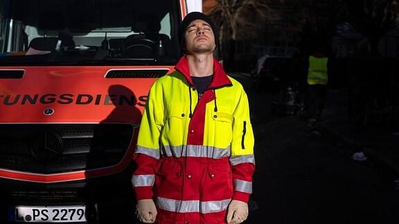 Jascha Rust vor einem Krankenwagen mit geschlossenen Augen