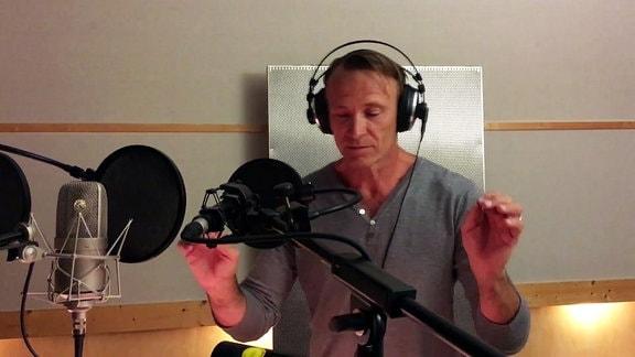 Mann mit Kopfhörern dirigiert