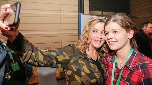 Schauspielerin Alexa Maria Surholt macht ein Selfie mit einem jungen Fan.