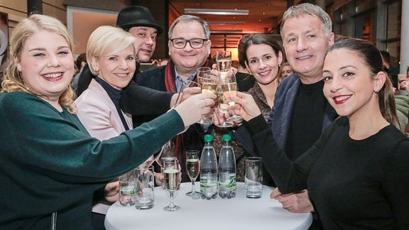 Lachende Schauspieler von In aller Freundschaft stoßen an bei der Premiere der IaF-Webserie.