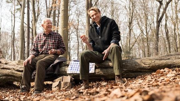 Rolf Becker und Bernhard Bettermann lachen bei Dreharbeiten im Wald