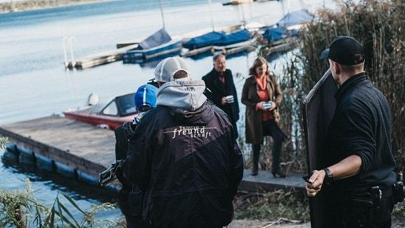 Schauspieler und Team bei Dreharbeiten am See