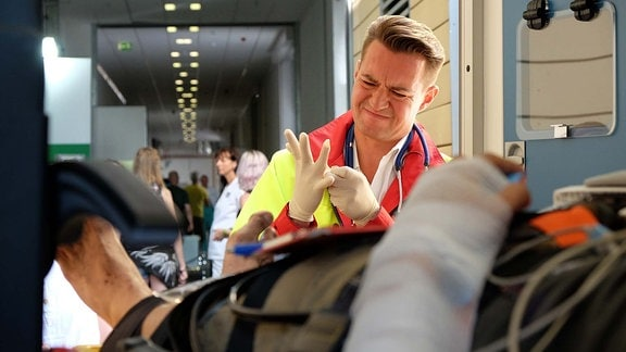 Markus Neumann versucht Handschuhe anzuziehen