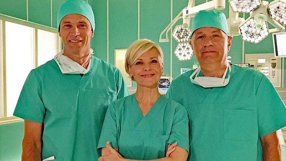 Drei Schauspieler in grüner OP-Kleidung am Set der Fernsehserie 'In aller Freundschaft'.