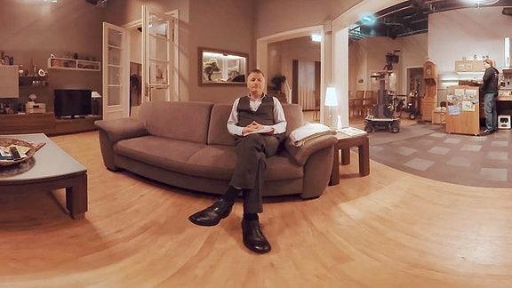 360 Grad Aufnahme im Studio von 'In aller Freundschaft', ein Schauspieler seitzt auf dem Sofa