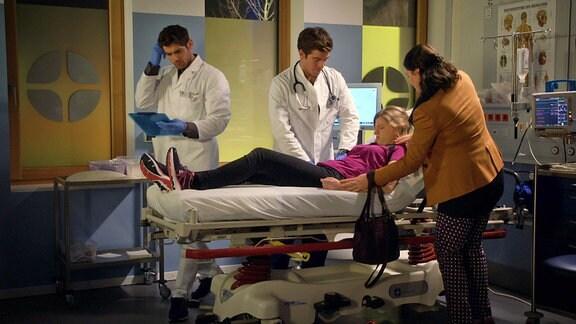 Zwei Ärzte und eine Frau neben einem Mädchen auf einem Krankenbett