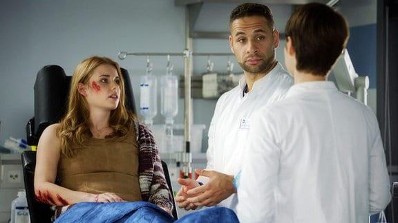 Zwei Ärzte neben junger Frau mit Schürfwunden