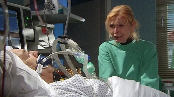 Eine Frau weint am Krankenbett eines Mannes.