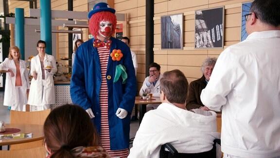 Patienten und Mediziner in einer Kantine, dazwischen ein Mann im Clownskostüm