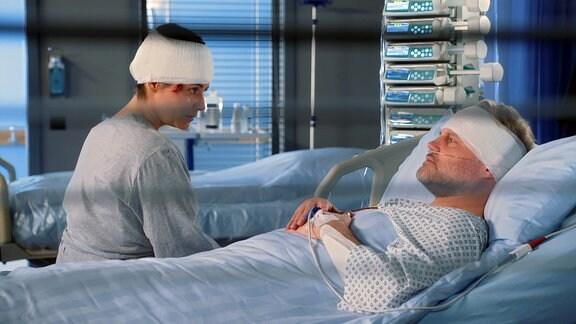 Frau mit Kopfverband sitzt am Krankenbett eines Mannes mit Kopfverband