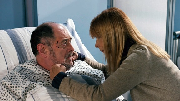 Eine Frau streichelt einen Mann, der in einem Krankenbett liegt.