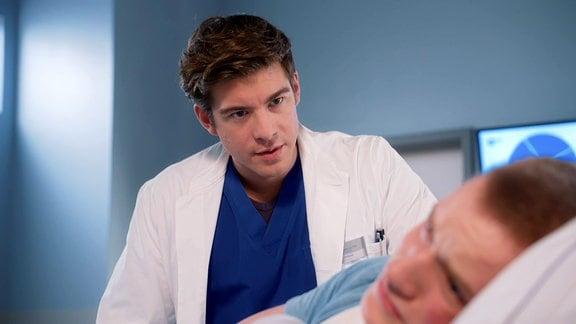 Arzt redet mit Mann im Krankenbett
