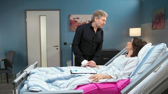 Mann hält Hand einer Frau in Krankenbett