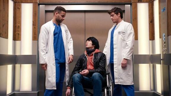 Zwei Ärzte und ein Mann im Rollstuhl in einem Aufzug