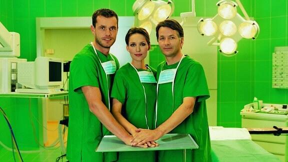 Joachim Kretzer, Ina Rudolph und Thomas Rühmann posieren im OP