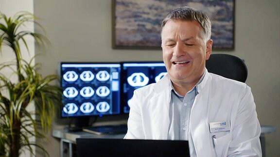 Dr. Roland Heilmann lacht mit Blick in den Computer.