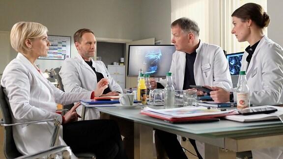 Dr. Maria Weber (Annett Renneberg, re.) schlägt in der Morgenkonferenz für eine schwangere Patientin einen chirurgischen Eingriff am Herzen ihres ungeborenen Kindes vor, falls die medikamentöse Therapie nicht anschlägt. Dr. Roland Heilmann (Thomas Rühmann, 2.v.re.) und Dr. Kathrin Globisch (Andrea Kathrin Loewig, li.) wissen, wie gefährlich das sein kann. Chefarzt Dr. Kai Hoffmann (Julian Weigend, 2.v.li.) möchte dafür eine versierte Fetalchirurgin anfragen. Dr. Weber hat das Gefühl, dass ihr zu wenig Vertrauen entgegengebracht wird, doch für Dr. Hoffmann ist das Thema damit beendet.