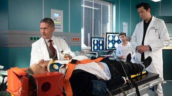 Dr. Brentano (Thomas Koch, re.) und Dr. Kaminski (Udo Schenk, li.) untersuchen den Patienten.