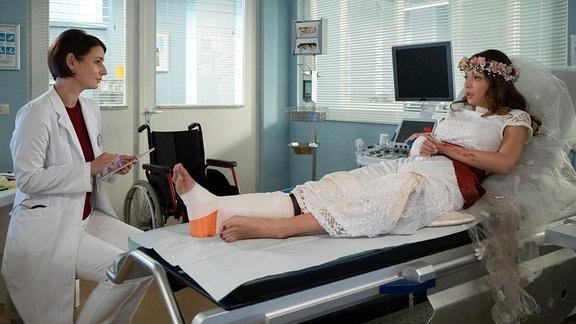 Dr. Maria Weber (Annett Renneberg, li.) kümmert sich um Nikki Schönau (Lena Meckel, re.), die sich bei einem Unfall mit dem E-Roller ihren Fuߟ gebrochen hat. Alles in allem hatte Nikki groߟes Glück, ihr Verlobter Hauke ist weitaus schwerer verletzt.