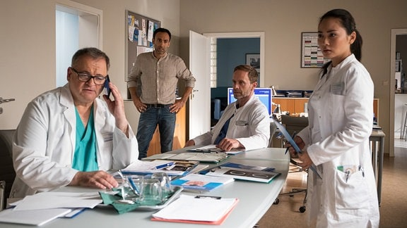 Hans-Peter Brenner (Michael Trischan, li.), Dr. Lilly Phan (Mai Duong Kieu, re.) und Dr. Kai Hoffmann (Julian Weigend, 2.v.re.) im Ärztezimmer mit Rajat Agarwal (Patrick Khatami, 2.v.li.).