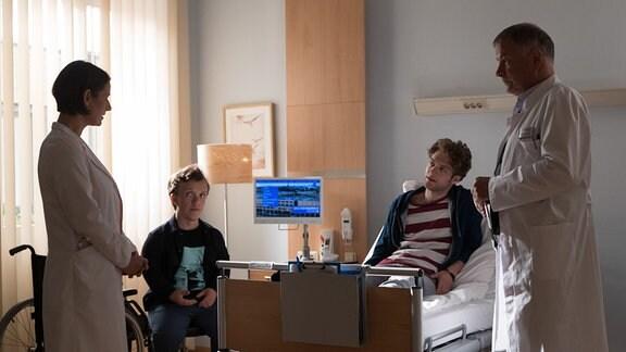 Leo Prinz (Dennis Svensson, 2.v.re.) spielt seine Schmerzen herunter, doch die Ärzte Dr. Maria Weber (Annett Renneberg, li.) und Dr. Roland Heilmann (Thomas Rühmann, re.) müssen operieren.