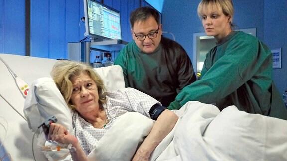 Hans-Peter Brenner (Michael Trischan, mi.) und Dr. Lea Peters (Anja Nejarri, re.) setzen eine Lumbalpunktion bei Renate Hardenberg (Lisa Kreuzer, li.) an.