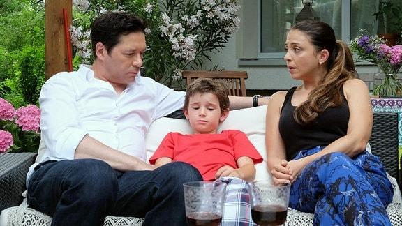 Philipp und Arzu reden auf dem Sofa mit ihrem Sohn Oskar.