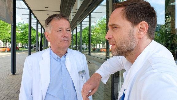 Dr. Roland Heilmann redet mit Dr. Kai Hoffmann.