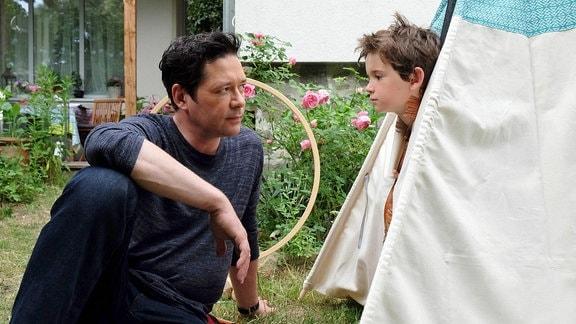 Philipp redet mit Oskar im Garten.