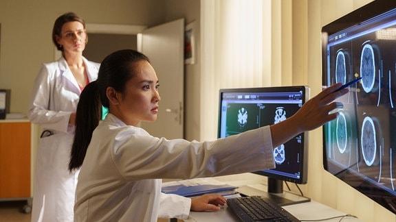 Dr. Lilly Phan zeigt auf einen Bildschirm.
