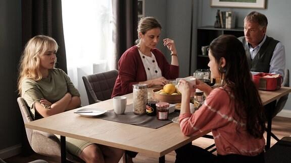 Die Familien Heilmann und Brückner sitzen zusammen am Tisch.