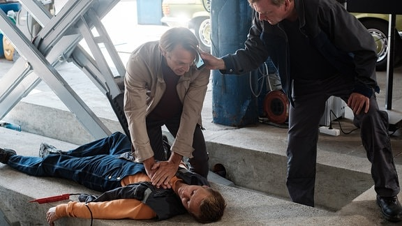 Dr. Martin Stein (Bernhard Bettermann, li.) bei der Herzdruckmassage bei Mick Mohnhaupt (Joseph Bundschuh, liegend)