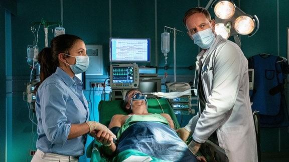 Dr. Kai Hoffmann (Julian Weigend, re.) behandelt Mick Mohnhaupt (Joseph Bundschuh, mi.). Oberschwester Arzu (Arzu Bazman, li.) unterstützt ihn.