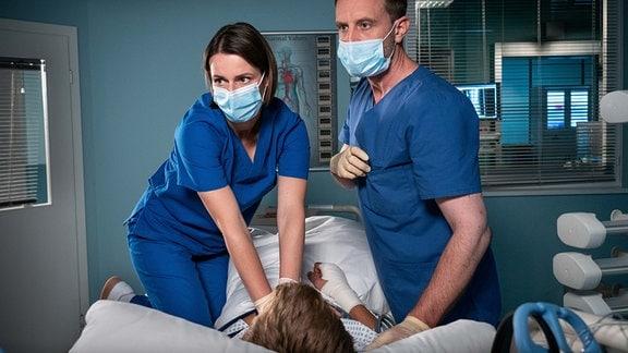Dr. Maria Weber (Annett Renneberg, li.) und Dr. Kai Hoffmann (Julian Weigend, re.) machen eine Herzdruckmassage.