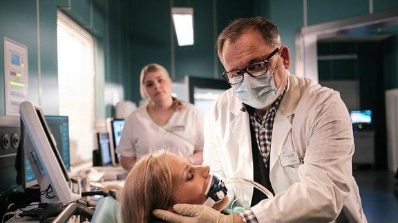 Dr. Hans-Peter Brenner (Michael Trischan, re.) untersucht die Patientin.