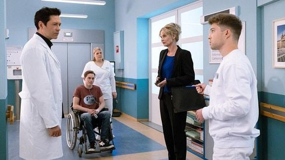 Kris Haas spricht mit Dr.Brentano und Franjos Mutter im Flur.