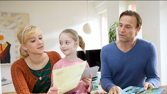 Martin Stein (Bernhard Bettermann, re.) freut sich nach turbulenten Wochen auf den gemeinsamen Familienurlaub. Als ein Brief von Sophies (Leni Johanna Trost, mi.) leiblichen Vater Christoph ankommt, schwindet diese Freude.