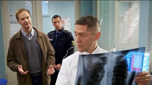 Dr. Rolf Kaminski (Udo Schenk, re.) traut seinen Ohren nicht, als Oberkommissar Erich Gassmann (Arnfried Lerche, li.) ihm sagt, dass ein Patient Anzeige gegen ihn erstattet hat.