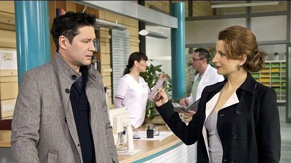Die Personalanwerberin Dr. Olivia Jung (Nadine Schori) sucht Dr. Philipp Brentano (Thomas Koch) in der Sachsenklinik auf (im Hintergrund Komparsen) und bietet ihm eine Oberarztstelle in Kalifornien an.