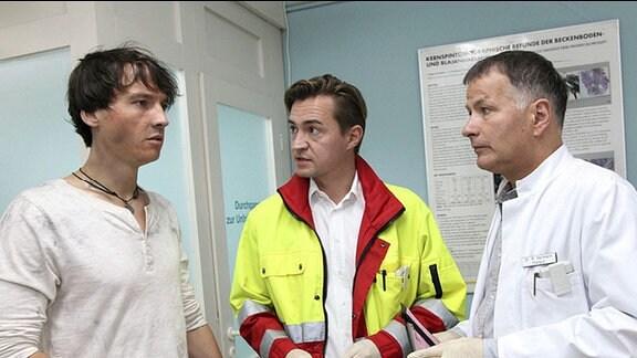 Gero Quitte (Ralph Kretschmar, li.) erkundigt sich bei dem Notarzt (Markus Neumann, mi.) und Dr. Roland Heilmann (Thomas Rühmann, re.) nach dem Zustand der eingelieferten Patientin Marlene Defland.