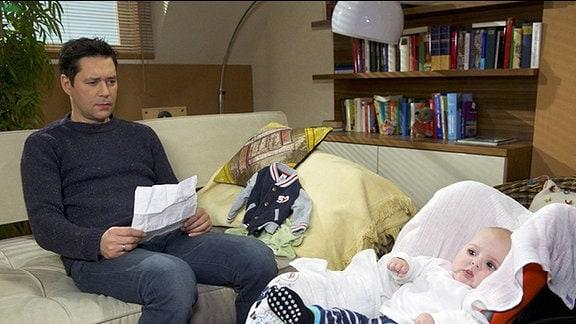 Philipp Brentano (Thomas Koch) sitzt zusammen mit Max im Wohnzimmer und betrachtet nachdenklich das Ergebnis des Vaterschaftstest.