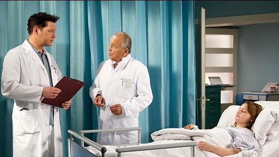 Amelie Richter liegt im Krankenbett. Dr. Philipp Brentano und Professor Simoni beraten gemeinsam am Bett.
