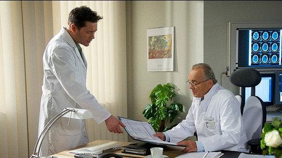 Dr. Philipp Brentano und Prof. Simoni beraten sich im Büro.