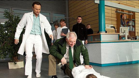 Ein Polizist drückt den Strafgefangenen Gunter Dahlke  zu Boden, Martin Stein und mehrere Leute Klinikpersonals steht daneben und beobachten die Szene.