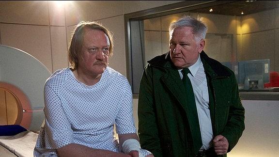 Sträfling Gunther Dahlke und Polizist Harald Zewen vor einem Tomografen. Gunther hat Patientenkleidung an und hat erfahren, dass er unbemerkt mehrere Schlaganfälle erlitten hat.
