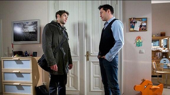 Niklas Ahrend und Philipp Brentano stehen sich in Philipps Wohnung gegenüber.