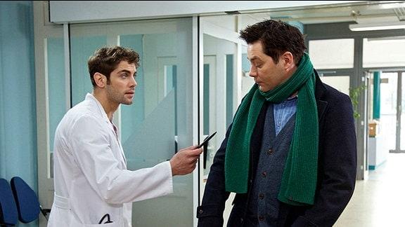 Niklas Ahrend macht Philipp Brentano Vorwürfe und zeigt drohend mit einem Kugelschreiber auf Philipp. Philipp schiebt einen Kinderwagen durch die Klinik.