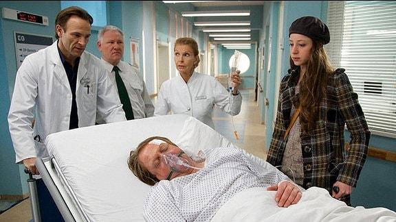 Dr. Stein und Oberschwester Ingrid schieben Sträfling Dahlke und sein Krankenbett in den Operationssaal. Tochter Nina und Justizvollzugsbeamten Harald Zewen stehen daneben.