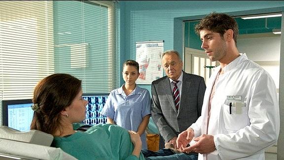 Gynäkologe Dr. Niklas Ahrend rät Rebecca Simoni, ihr Kind per Kaiserschnitt auf die Welt zu bringen. Schwester Arzu und Rebeccas Vater Professor Simoni bestärken Dr. Ahrend.