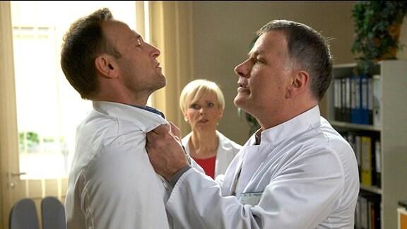 Roland Heilmann (Thomas Rühmann, re.) geht im Ärztezimmer auf Martin Stein (Bernhard Bettermann, li.) los. Kathrin Globisch (Andrea Kathrin Loewig, mi.) ist entsetzt.